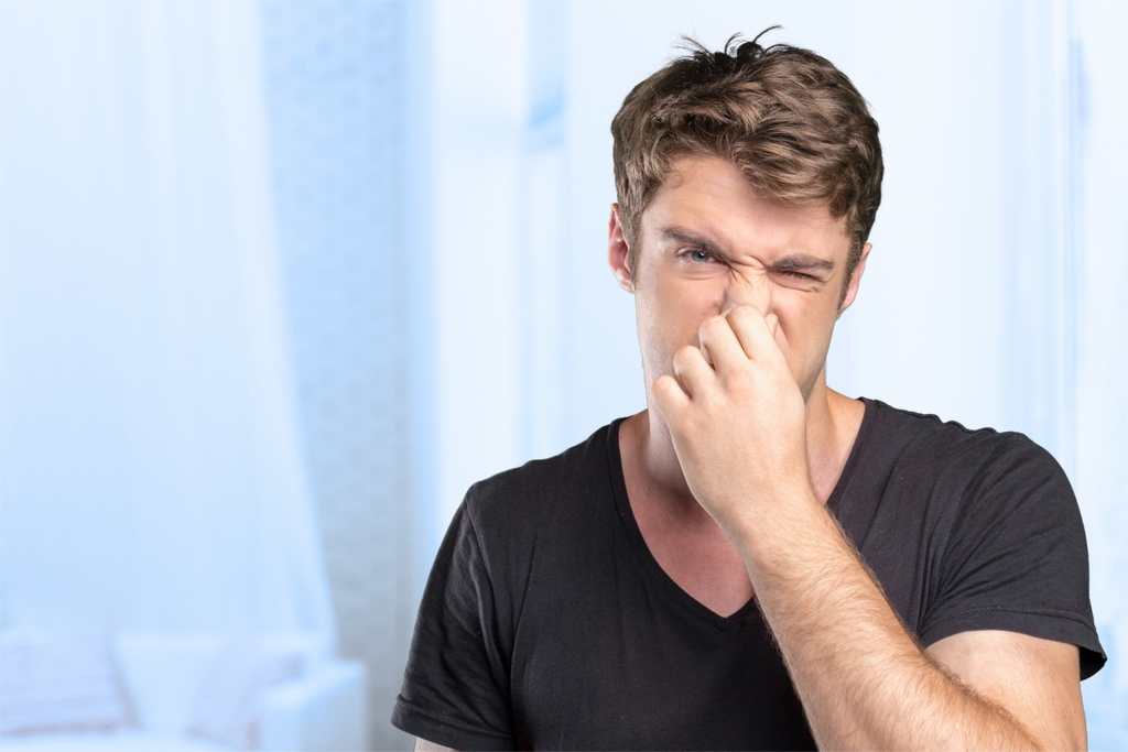 Young Man holding his nose against a bad smell