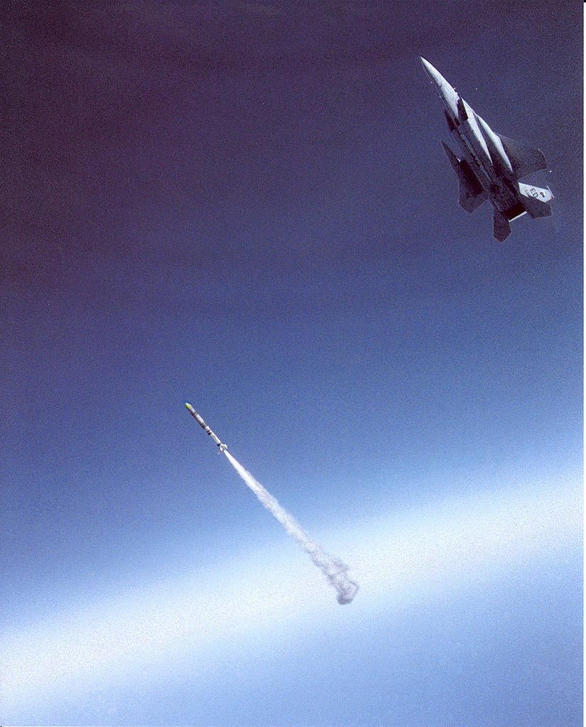 """F-15A Eagle aircraft piloted by Major Wilbert """"Doug"""" Pearson firing a missile at a satellite with the missile igniting."""