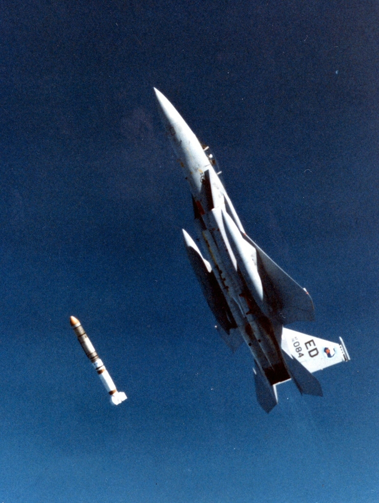 """F-15A Eagle aircraft piloted by Major Wilbert """"Doug"""" Pearson firing a missile at a satellite."""